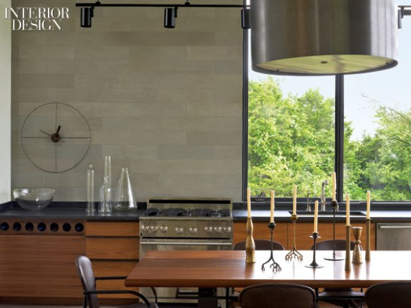 409159-An_8_foot_long_vintage_dining_table_serves_the_kitchen_which_has_custom_walnut_cabinetry_and_a_wall_clad_in_limestone_tile